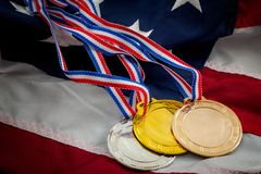 Olympic glory and triumph in sports competition concept with three medals gold, silver and bronze on the USA flag, representing. The success of american stock images