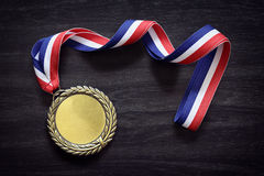 Olympic gold medal. Gold medal on black wood background with blank face for text, concept for winning or success Royalty Free Stock Photography