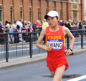 Olympic marathon. London, UK - August 05, 2012: J. Wang, a long-distance runner representing China, competes in the London 2012 Olympics Women's Marathon Royalty Free Stock Photos