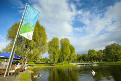 Olympic Park in Munich. MUNICH, GERMANY - MAY 6, 2017 : A view of the trees and lake with gooses and swans in the Olympic Park in Munich, Germany Stock Image
