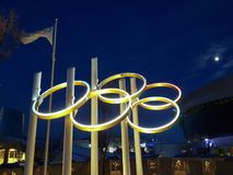 Olympic rings and flag by night. Montral, Canada Stock Photo