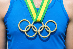 Olympic Rings Gold Medal Brazil Ribbon. RIO DE JANEIRO, BRAZIL - FEBRUARY 4, 2015: Olympic rings gold medal hangs from Brazil colors ribbon on the chest of an Stock Images