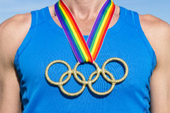 Olympic Rings Gold Medal Gay Ribbon. RIO DE JANEIRO, BRAZIL - FEBRUARY 4, 2015: Olympic rings gold medal hangs from gay pride rainbow ribbon on the chest of an Stock Images