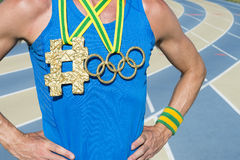 Olympic Rings Gold Medal Hashtag Athlete. NEW YORK CITY, USA - AUGUST 20, 2015: Olympic rings gold medal hangs next to hashtag from Brazil colors ribbons on the Stock Photography