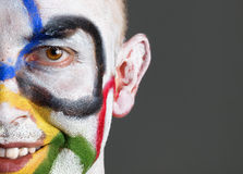 Olympic rings painted on the face of smiling man. Olympic rings painted on the face of man. The man is smiling and isolated on a dark background, looking at Stock Photos