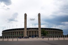 Olympic rings symbol hanging over Olympic stadium in Berlin, Germany. Olympic rings symbol hanging over Olympic stadium from 1936 in Berlin, Germany, dramatic Royalty Free Stock Images