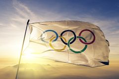 Olympic rings with transparent rims flag textile cloth fabric waving on the top sunrise mist fog. Beautiful royalty free stock photos