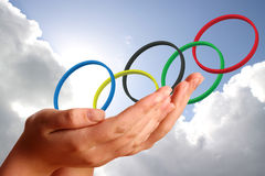 Olympic rings  in young womans hands. Against the sky Stock Images