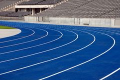 Stadium. Eight blue tracks of the stadium, seats area on the background Stock Photos