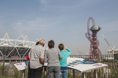 Olympic Stadium. LONDON, UK – MARCH 24: Visitors looking at Olympic Stadium and Anish Kapoor sculpture in the background on March 24, 2012 in London. The Stock Image