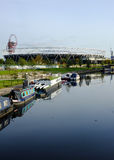 East London, UK: Olympic Stadium from River Lea, Portrait, Stratford. The Olympic Stadium from the River Lea, with canal boats. At Hackney Wick Royalty Free Stock Images