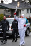 Olympic Torch Bearer. A happy torch bearer runs with the Olympic Flame for the 2010 Vancouver Olympic games stock photography