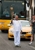 Olympic Torch Relay. Unidentified Torch Bearer carrying the Olympic Torch through Inverness, Scotland, on it's nationwide relay ahead of the 2012 Games in London Stock Photography