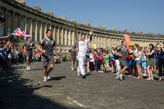Olympic torch relay 2012,Bath, UK. BATH, UK - MAY 22, 2012: Christopher Phillips,(centre) carries the Olympic Torch around the Royal Crescent on May 22, 2012 in Stock Photography