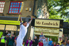 Olympic torch relay runner, Headingley, Leeds, UK. Crowd on street watching the Olympic torch carried by a running torchbearer sportsman - actor Glenn Lamont Stock Photo