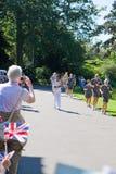 Olympic Torchbearer in Kew Gardens. Kew Gardens, London - 24th July, 2012: Torchbearer no 46 runs through Kew Gardens, Richmond Royalty Free Stock Photos