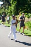 Olympic Torchbearer in Kew Gardens. Kew Gardens, London - 24th July, 2012: Torchbearer no 46 runs through Kew Gardens, Richmond Royalty Free Stock Photography