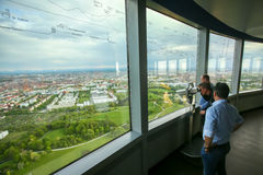 Olympic Tower Munich. MUNICH, GERMANY - MAY 6, 2017 : People looking at the cityscape through the binoculars at the observation platform of the Olympic Tower in Stock Photography
