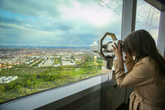 Olympic Tower Munich. MUNICH, GERMANY - MAY 6, 2017 : A woman looking at the cityscape through the binoculars at the observation platform of the Olympic Tower in Royalty Free Stock Photos