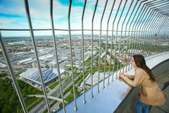 Olympic Tower Munich. MUNICH, GERMANY - MAY 6, 2017 : A woman looking at the cityscape with BMW Museum at the observation platform of the Olympic Tower in the Stock Images