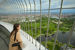 Olympic Tower Munich. MUNICH, GERMANY - MAY 6, 2017 : A woman looking at the cityscape at the observation platform of the Olympic Tower in the Olympic Park in Royalty Free Stock Images