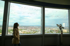 Olympic Tower Munich. MUNICH, GERMANY - MAY 6, 2017 : A woman looking at the list of buildings on the glass at the observation platform of the Olympic Tower in Royalty Free Stock Photography