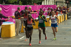 Olympic Women's Marathon Leaders. The leaders of the 2012 Olympic Women's marathon pass the Cannon Street Water Station for the last time. Mary Jepkosgei KEITANY Royalty Free Stock Photo
