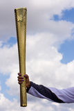 Olympics. London-July 21st: Unidentified torch bearer holds up the olympic torch on the 21st July 2012. The Olympics is a major sporting event around the world Royalty Free Stock Photography