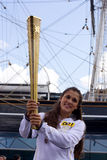 Olympics. London-July 21st: Unidentified torch bearer holds up the olympic torch by cutty sark on the 21st July 2012. The Olympics is a major sporting event Stock Photography