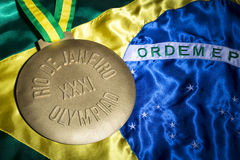 Olympics-Goldmedaille Rios 2016 auf Brasilien-Flagge Stockfotografie