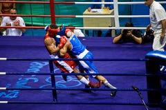 Olympische Boxer fallen während des Kampfes Stockbilder