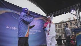 Olympische Fackel Staffellauf-Sochis in St Petersburg Wirt auf Stadium Torchbearer mit nicht Brandflamme stock footage