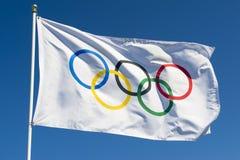 Olympische Flagge, die im hellen blauen Himmel flattert Stockfoto
