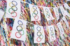 Olympische Flaggen-Flagge, die vor brasilianischen Wunsch-Bändern hängt Stockfotos