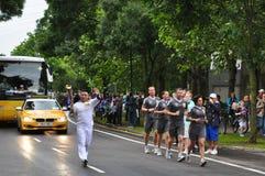 Olympische Flamme getragen vom Torchbearer Lizenzfreie Stockbilder