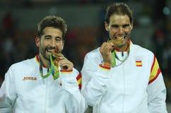 Olympische kampioenen Mark Lopez en Rafael Nadal van Spanje tijdens medailleceremonie na overwinning bij de dubbelendef. van mens Stock Afbeeldingen