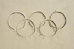 Olympische Ring-Mitteilung gezeichnet in Sand Lizenzfreie Stockfotografie