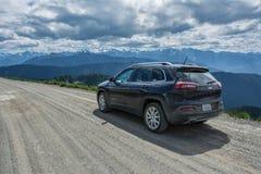 Olympisk nationalpark, Washington, USA - Juni 17, 2015: Jeep Cherokee på en landsväg i bergen av den olympiska nationalparken Royaltyfri Fotografi