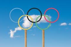 Olympiska cirklar står under ljus iin för blå himmel en golfbana Royaltyfri Fotografi