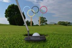 Olympiska cirklar står under ljus iin för blå himmel en golfbana Royaltyfri Foto