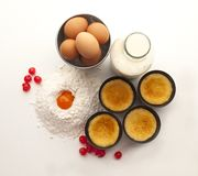 Still life with flour, eggs, currants a bottle of milk and four custards in their molds royalty free stock images