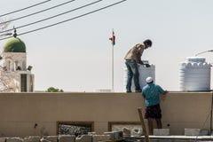 Omã Salalah 17 10 2016 povos que trabalham na frente da bandeira ubar da região da montanha de Dhofar da torre da mesquita Fotos de Stock