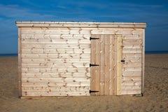 Omålad strandkoja Nytt träskjul på sanden Arkivbild