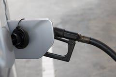 Om de auto met brandstof te vullen, sluit omhoog stock afbeelding