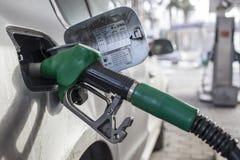 Om de machine met brandstof te vullen Mashunya vult met benzine bij een benzinestation De pomp van het benzinestation Mens het vu Stock Afbeelding