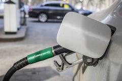 Om de machine met brandstof te vullen Mashunya vult met benzine bij een benzinestation De pomp van het benzinestation Mens het vu Stock Fotografie