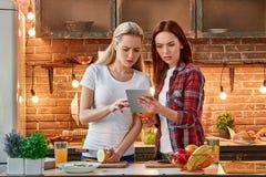 Om du inte kan uttala det, äta inte det Unga kvinnliga vänner som tillsammans förbereder sunt mål i modernt kök cozy royaltyfria foton