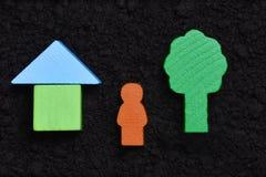 Om een Mens te zijn, bouw huis, installatieboom, vaderkind Houten symbolen op grondachtergrond royalty-vrije stock foto's