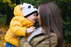 Om hugging young child daughter in autumn park. Close up portrait. royalty free stock image