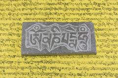 Om mani padme hum. The most popular Tibetan mantra Om Mani Padme Hum engraved on a stone. On a yellow background with Tibetan writings. Om mani padme hum is the Royalty Free Stock Image